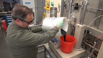 PNNL lab manager Todd Hart pours wet biomass into a bucket as he begins an experiment to convert the substance into biocrude oil. Photo Courtesy of PNNL.