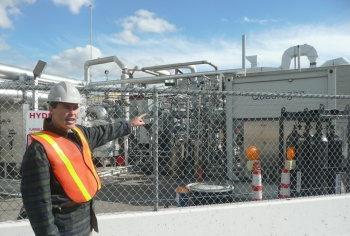 Professor Jack Brouwer, Associate Director and Chief Technology Officer of the National Fuel Cell Research Center, points out the tri-generation facility that uses biogas from Orange County Sanitation District's wastewater treatment plant to produce hydrogen, heat and power. | Photo courtesy of the Energy Department.