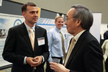 William Parish from Solar Mosaic, one of nine solar startups chosen for the latest round of SunShot Incubator funding, discusses his company's project with Energy Secretary Steven Chu at the SunShot Grand Challenge Summit in Denver, Colorado.   Photo by John De La Rosa.