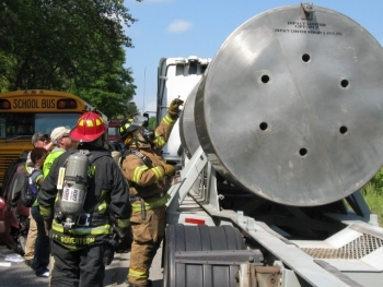 A firefighter trained to respond to radiological events performs a radiological survey of the WIPP shipping package as part of a WIPP transportation exercise in Morgan County, Georgia.
