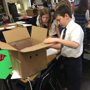 Students at St. Agnus Catholic School in Arlington, Va., measure weatherstripping to place around doors and windows