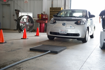 Researchers from Oak Ridge National Laboratory test a wireless charger on the fully-electric Toyota Scion iQ at a demonstration site.   Photo courtesy of Oak Ridge National Laboratory
