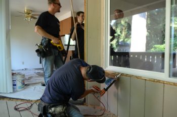 A worker caulks the exterior of a home window. Advanced window framing techniques can help homeowners save energy and money. | Photo courtesy of Weatherization Assistance Program Technical Center