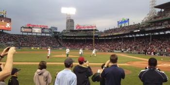 """Secretary Moniz, far right, throws the first pitch at the Red Sox Earth Day game on April 22, 2014.   Photo by <a href=""""/node/716056"""">Marissa Newhall</a>, Energy Department."""