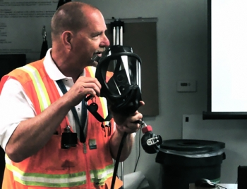 Advanced Mixed Waste Treatment Project Industrial Hygiene Manager Roger Raymond demonstrates breathing equipment. The specially-designed breathing equipment includes a primary face-piece and a second stage face-piece regulator, which is attached to a manifold configured with dual air supply (main and secondary), a vortex cooler, and an escape bottle. This configuration allows workers to safely enter atmospheres in excess of 100,000 derived air concentration levels.