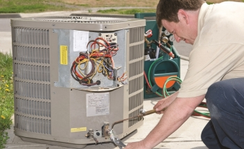 A technician installs central air conditioning equipment. Image courtesy of Pacific Northwest National Laboratory.