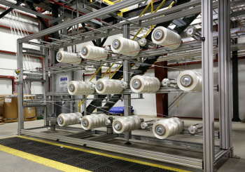 The facility will produce up to 25 tons of carbon fiber a year -- enough to satisfy R&D requirements while enabling large-scale manufacturing of carbon fiber products. Pictured here is the first stage in the carbon fiber production process, where spooled precursor material is fed into the conversion line. Precursor material may be spun into rolls or blown into a mat form before being conveyed through the stabilization, carbonization, and surface treatment steps of the process. | Photo courtesy of Oak Ridge National Laboratory.