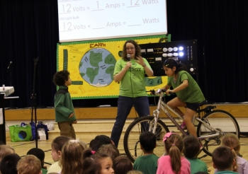 """In celebration of Earth Day in April, elementary school students at Churchill Road Elementary School in McLean, Virginia, learned about energy literacy by riding the Energy Department's energy bike. The bike enabled students to pedal for power and experience the difference in physical effort necessary to power incandescent, compact fluorescent, and LED lighting.  This lesson highlighted  Energy Principle 4, which states that various sources of energy can be used to power human activities, and often this energy must be transferred from source to destination. <a href=""""http://www.energyliteracyprinciples.org/"""">Check out energyliteracyprinciples.org</a> for more Energy Literacy lessons and activities.  