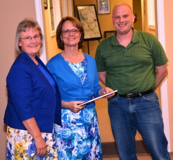 Judy Clayton, project leader and a member of the Paducah Citizen's Advisory Board (CAB), along with the CAB Vice Chair Ben Peterson, present a copy of the book to Cate Alexander (center), Designated Federal Officer of the EM Site-Specific Advisory Board.