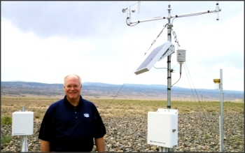 DOE Site Manager Rich Bush explains the Enhanced Cover Assessment Project to Colorado Mesa University students while standing next to one of LM's Systems Operation and Analysis at Remote Sites locations, which collects data remotely and transmits it to LM servers daily.