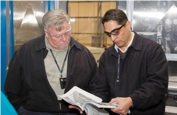 EM Deputy Assistant Secretary for Waste Management Frank Marcinowski, left, talks with LANL's Oversized Container Disposition Project Manager Mike Romero while on a tour of the 375 box line facility in late February.