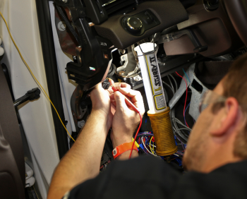 A team member from the Embry Riddle Aeronautical University team checks the main point of connection of the low voltage system. This connection allows communication with the charger, eventually ensuring the vehicle's battery will stay charged. | Photo courtesy of EcoCAR 2.