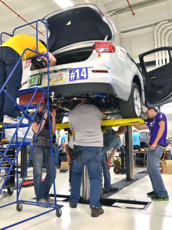 The University of Washington team works on their vehicle while lifted on a hoist. Teams are working in a garage that is fully equipped with tools that will help them make the most of their time this week. | Photo courtesy of EcoCAR 2.