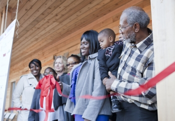 """One of the new homeowners, Layika Culley, and her family cut the ribbon to her new ultra-efficient home in the historic Deanwood neighborhood. For more photos of the Empowerhouse ribbon cutting, <a href=""""/node/580963"""">view our photo gallery</a>. 