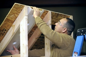 Daniel Tello demonstrates how to prepare an attic space for insulation using skills learned from the First Choice Program. | Photo courtesy of HCDC, Human Capital Development Corp., Inc. and Scott Anderson