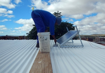 A worker paints a rooftop with reflective paint in the !Khies municipality in Northern Cape, South Africa.   Photo by Mothusi Guy of PEER Africa