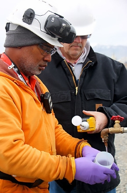 Workers sample a well used to monitor groundwater at the Hanford site.