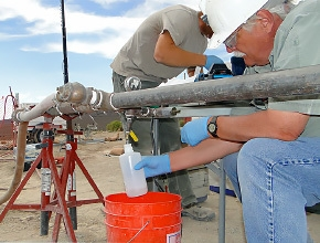 A specialist with the Nevada National Security Site groundwater characterization team collects a groundwater sample at well PM-3 located on the Nevada Test and Training Range, which is Air Force controlled land surrounding the NNSS. Groundwater characterization activities address the impacts of historic nuclear testing on groundwater.