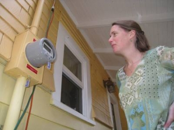 Laura Smoyer checks the net-metering device in her home, which now uses the sun for about 38 percent of its total energy use.     Department of Energy Photo  