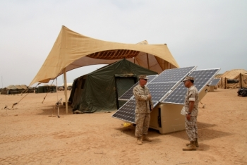 Maj. Sean M. Sadlier (left) of the U.S. Marine Corps Expeditionary Energy Office explains the solar power element of the Expeditionary Forward Operating Base concept to Col. Anthony Fernandez during the testing phase of this sustainable energy initiative. | Photo Courtesy of U.S. Marine Corps | Photo by Maj. Paul Greenberg |