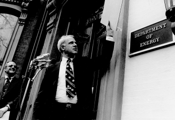 Dr. James R. Schlesinger, the first Secretary of Energy, unveils the signplate at the Energy Department's temporary headquarters on October 1, 1977.