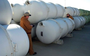 Workers inspect cylinders containing depleted uranium hexafluoride.