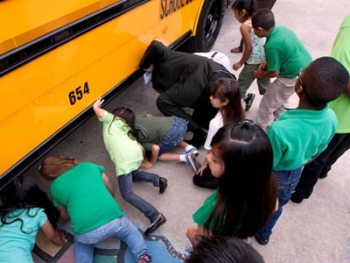 Students look underneath one of Fort Worth Independent School District's new hybrid diesel buses. | Photo courtesy of FWISD