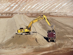A haul truck carrying a container is loaded with mill tailings at the Moab site. Once loaded and lidded, the container will be placed on a railcar for shipment by train to the Crescent Junction disposal site.