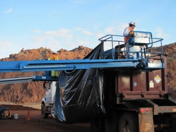 Laborers place a disposable liner in a tailings container.