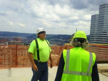 Century Steel Ironworker Al Williams escorts Secretary Moniz to the top floor of the construction site to show the work he and his team are completing during a visit to Pittsburgh on Monday, July 21, 2014.