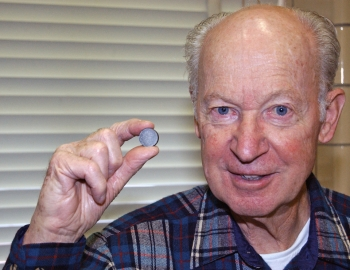 Dr. Karl Gschneidner is holding a neodymium-iron-boron magnet produced using a new, greener process. The process that Dr. Gschneidner helped develop doesn't produce the environmentally unfriendly byproducts that result from traditional manufacturing methods. | Photo courtesy of Ames Laboratory.