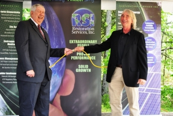 Oak Ridge Mayor Tom Beehan, left, and RSI Vice President Rick Ferguson pose for photos at a May 2012 ceremony for an RSI solar farm at DOE's East Tennessee Technology Park.