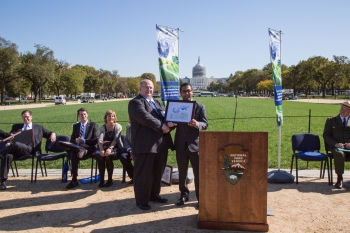 William Davis, the director of the National Alternative Fuels Training Consortium that organizes Odyssey Day, recognizes the Department of Energy's contributions towards promoting alternative fuel vehicles with DOE's Deputy Assistant Secretary for Transportation Reuben Sarkar.