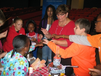 Sixth graders compare emissions from a candle—invisible until they hold a mirror close to the flame and watch carbon blacken its surface. The same mirror grows steamy but clear when held up to the water vapor piping out of the tea kettle. Sharon Cosgrove, of the Energy Department's Geothermal Technologies Office, talks with the students about energy options: burning hydrocarbons to boil water and generate steam or letting the Earth heat water naturally with geothermal energy.  | Photo courtesy of Old Mill Middle School North