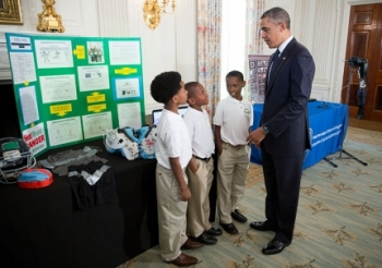 President Barack Obama talks with Evan Jackson, 10, Alec Jackson, 8, and Caleb Robinson, 8, from McDonough, Ga., while looking at exhibits at the White House Science Fair in the State Dining Room, April 22, 2013. The sports-loving grade-schoolers created a new product concept to keep athletes cool and helps players maintain safe body temperatures on the field.   Official White House Photo by Chuck Kennedy.