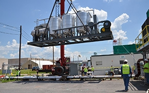 A carbon regeneration unit is lowered into place for above ground treatment at the C-400 Cleaning Building. Watch a video of this work here.