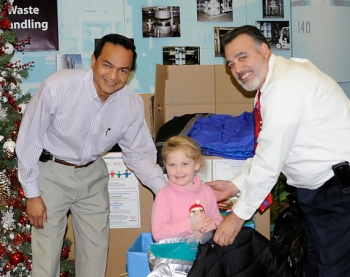 Aspen Cass, a relative of an EM Carlsbad Field Office (CBFO) employee, holds donated coats with Farok Sharif (left), president and project manager of Nuclear Waste Partnership, the WIPP management and operating contractor, and Joe Franco, manager of CBFO.