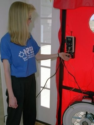 Kendra now works in weatherization, part of which often includes using blower door testing equipment to find air leaks, much like the equipment used here by an NREL worker. | File photo