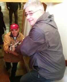 John Rizzo passes canned food to John Rendall to deliver to a food pantry.