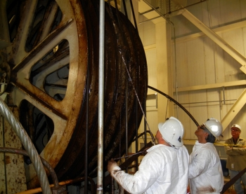 WIPP surface maintenance employees tail a new steel head rope over the hoist drum. The hoist is used to transport TRU waste 2,150 underground for final disposal.