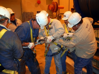 The WIPP shaft crew installs rigging onto a new 2,300-foot-long head rope on the first floor.