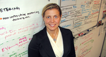 """PNNL Lab Homes researchers Sarah Widder stands in front of the """"brainstorming board"""" in her office. Many of these ideas have been generated by utilities, other researchers and the public as part of a workshop PNNL held during the ribbon-cutting ceremony for the Lab Homes two years ago. To submit your ideas on the technologies researchers should test, visit <a href=""""http://labhomes.pnnl.gov/"""">labhomes.pnnl.gov</a>. 