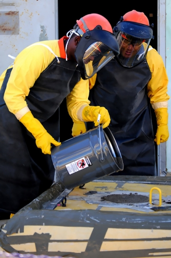 SRR employees Glenn Kelly and Fred Merriweather pour the final amount of grout into Tank 6.