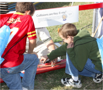 Students experiment with steel balls on a track as they learn about energy exchange during collisions during the USA Science and Engineering Festival held on the National Mall October 23-24.