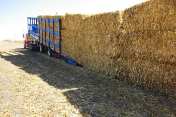 The self-loading trailer can automatically load or unload these large packs of bales -- made of biomass feedstocks -- in less than 15 minutes, reducing time and additional equipment needed to distribute the material to a biorefinery. | Photo courtesy of Antares Group.
