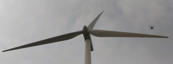 An automated drone inspects a wind turbine blade for damage. Photo|SkySpecs