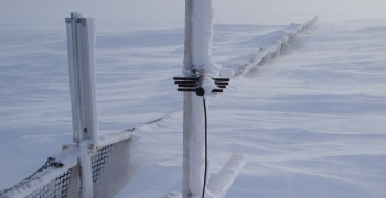 Monitoring equipment and part of the snowfence peek out of the snow drift.
