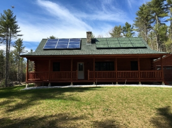 This shows side-by-side comparison shows traditional solar panels and Sistine Solar's new SolarSkin panels. The blue panels on the left are a stark contrast to this log cabin's green roof while the color match solar panels on the right blend in with the green roof. | Photo courtesy of Sistine Solar