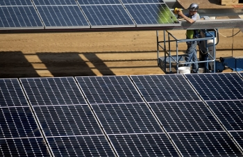 Workers install the parking lot solar panels at West Village at UC Davis. | Photo from UC Davis ARM