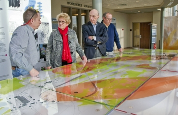 Steve Hampson of the University of Kentucky, left to right, West Kentucky Community & Technical College President Dr. Barbara Veazey, Paducah Junior College Board of Trustees member Ken Wheeler and Buz Smith of the DOE Paducah Site Office examine a DOE Paducah Site groundwater model exhibit at the West Kentucky Community & Technical College Emerging Technology Center.